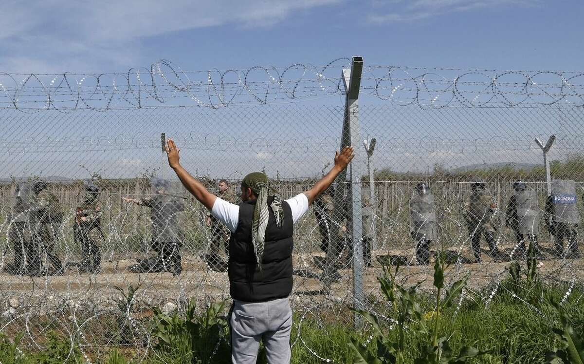 A migrant man shouts slogans during a protest at the fence at the northern Greek border point of Idomeni, Greece, Sunday, April 10, 2016. Thousands of migrants protested at the border and clashed with Macedonian police. (AP Photo/Amel Emric)