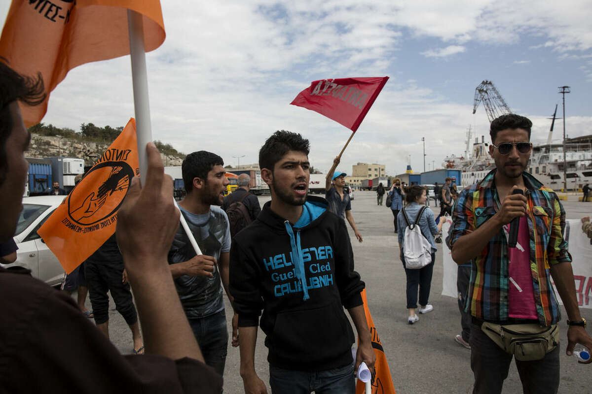 Migrants and refugees shout slogans during a rally against the closure of the border with Macedonia, at the port of Piraeus, near Athens, on Sunday, April 10, 2016. Migrants clashed with Macedonian police Sunday after trying to scale the fence separating Greece from Macedonia in the border town of Idomeni. (AP Photo/Yorgos Karahalis)