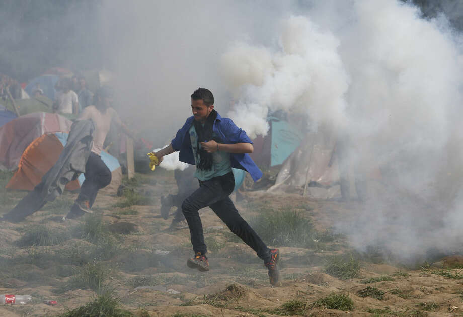 Migrant man runs with a tear gas canister during clashes with Macedonian police during a protest at a fence at the northern Greek border point of Idomeni, Greece, Sunday, April 10, 2016. Some thousands of migrants protested at the border and clashed with Macedonian police. (AP Photo/Amel Emric)