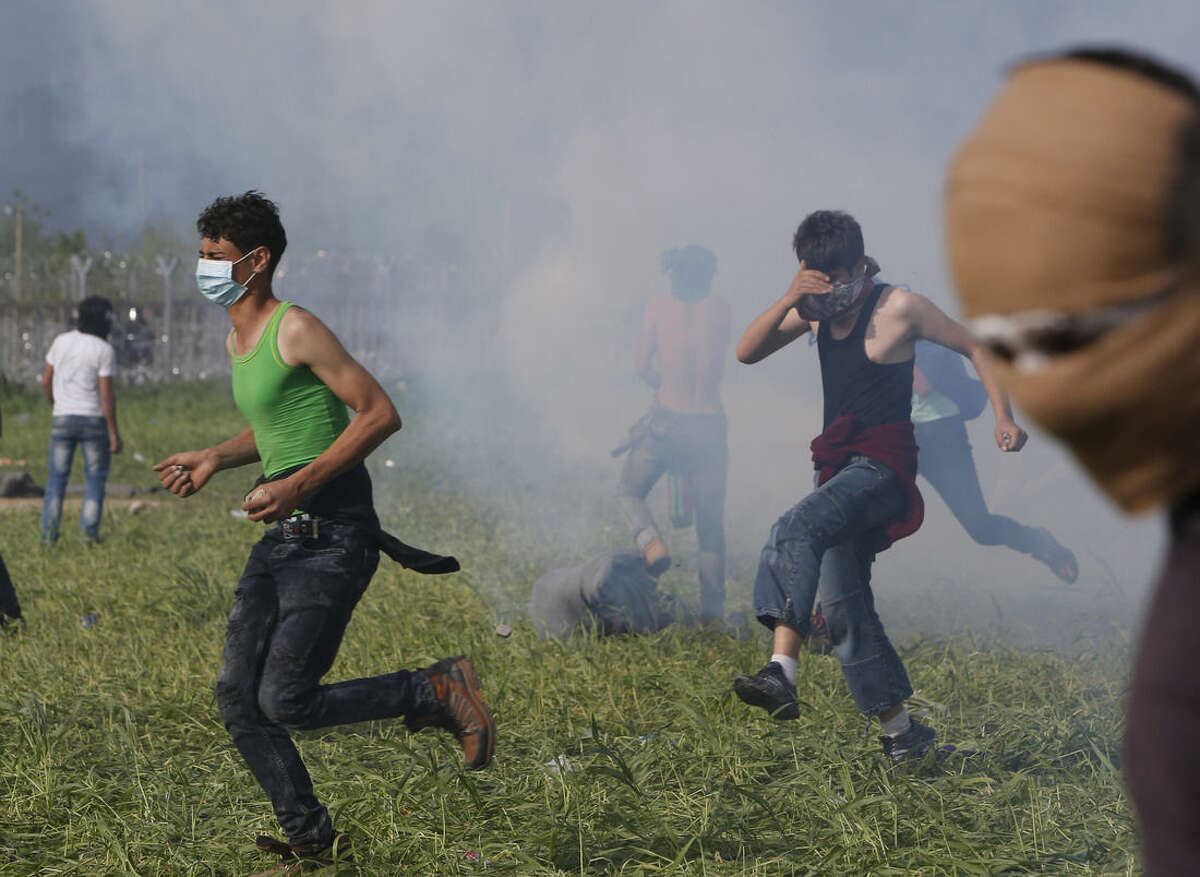 Migrant men run from tear gas during protests at a border control fence with Macedonia, at the northern Greek border point of Idomeni, Greece, Sunday, April 10, 2016. Thousands of migrants protested at the border and clashed with Macedonian police. (AP Photo/Amel Emric)