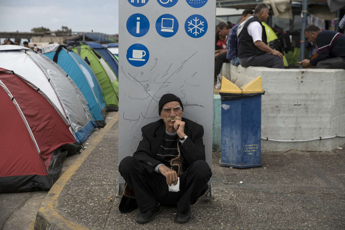 An elderly man sits in front of an information board at the port of Piraeus, near Athens, on Sunday, April 10, 2016. Migrants clashed with Macedonian police Sunday after trying to scale the fence separating Greece from Macedonia in the border town of Idomeni. (AP Photo/Yorgos Karahalis)