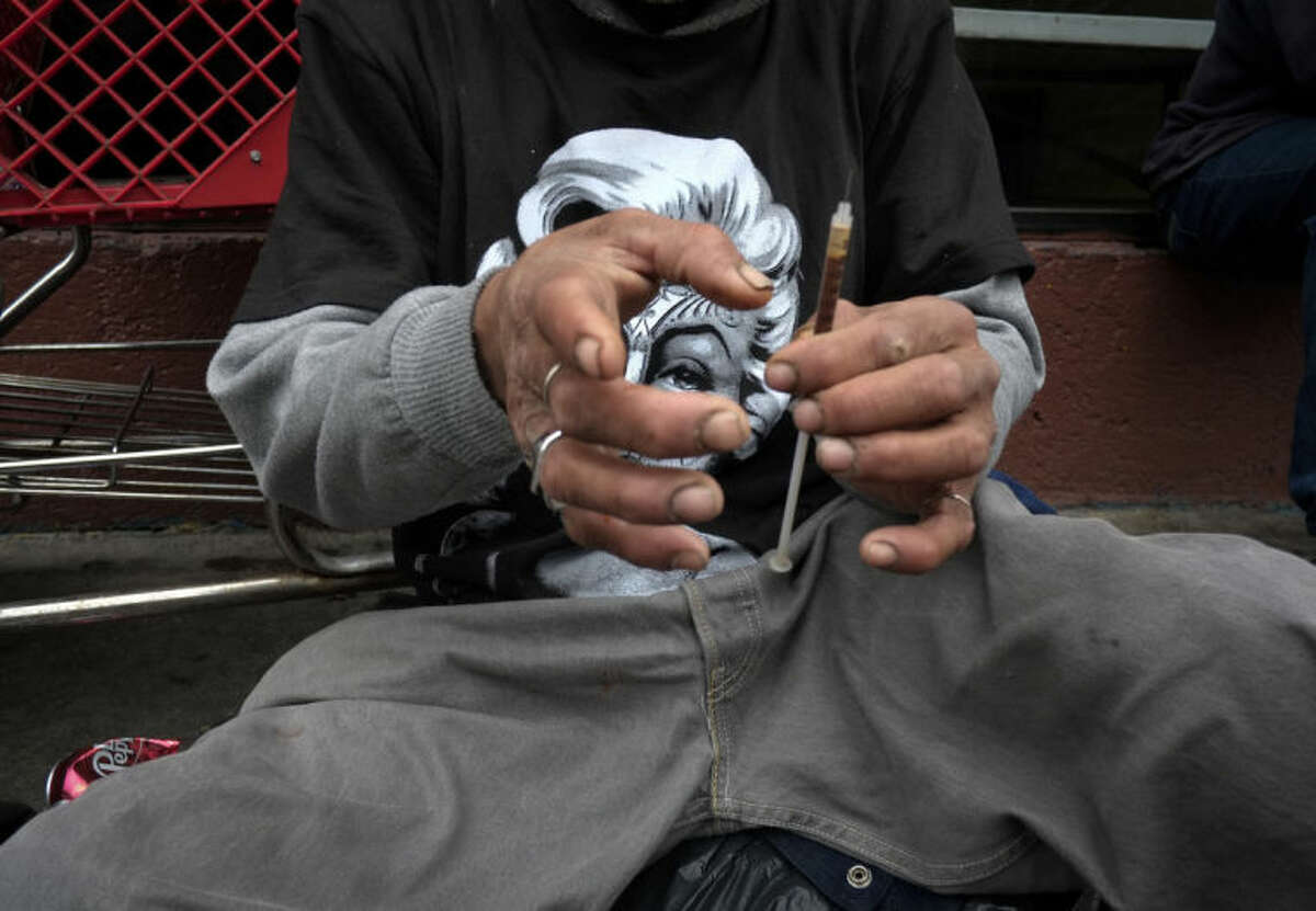 FILE - In this Monday, May 6, 2013 file photo, a drug addict prepares a needle to inject himself with heroin in front of a church in the Skid Row area of Los Angeles. The death of actor Philip Seymour Hoffman in February 2014 spotlighted the reality that heroin is no longer limited to the back alleys of American life. Once mainly a city phenomenon, the drug has spread to the country and suburbs. (AP Photo/Jae C. Hong)