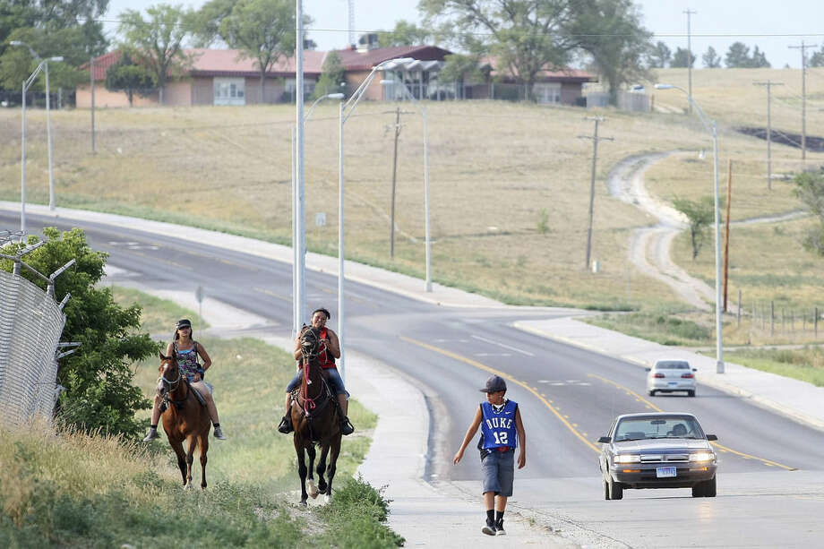 In this July 5, 2012 photo, Chantel Roubideaux, left, and Zaniya White Dress ride their horses into Pine Ridge, South Dakota, as Steven Brewer walks with them. Life for members of the Oglala Sioux Tribe is hard and suicide has been a persistent problem for the 16,000 and 30,000 people who live on the nation's eighth largest reservation. (AP Photo/Rapid City Journal, Ryan Soderlin)