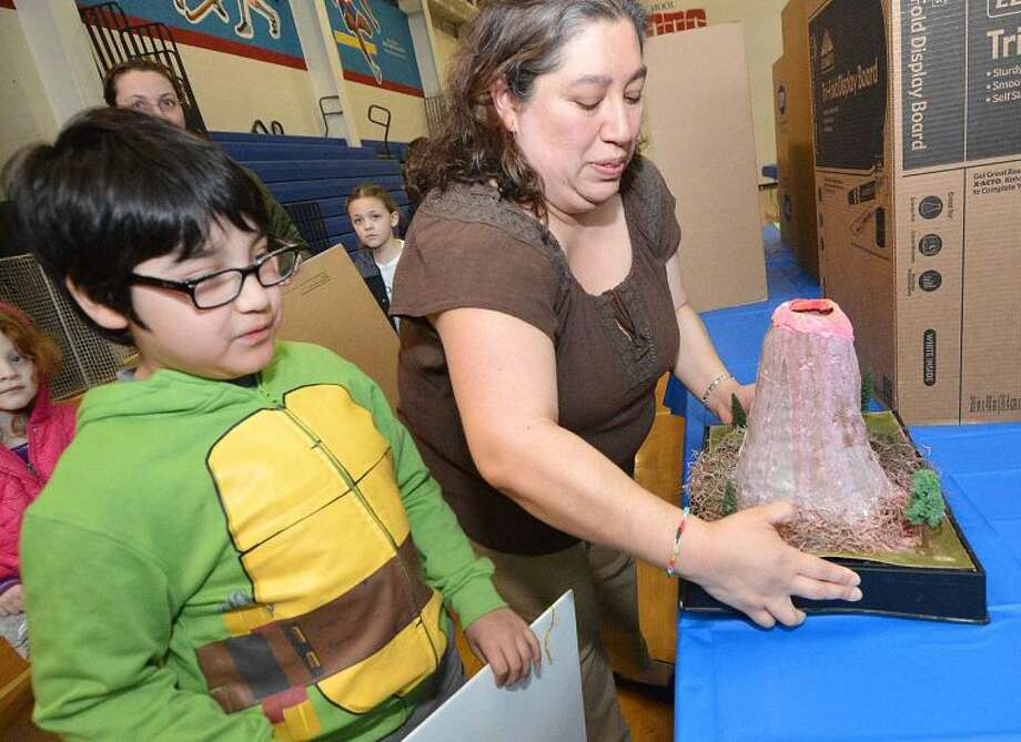 Hour Photo/Alex von Kleydorff Sandra Rosales helps her son 8yr old Gabriel set up his exhibit at the Citywide Science Fair at Brien McMahon