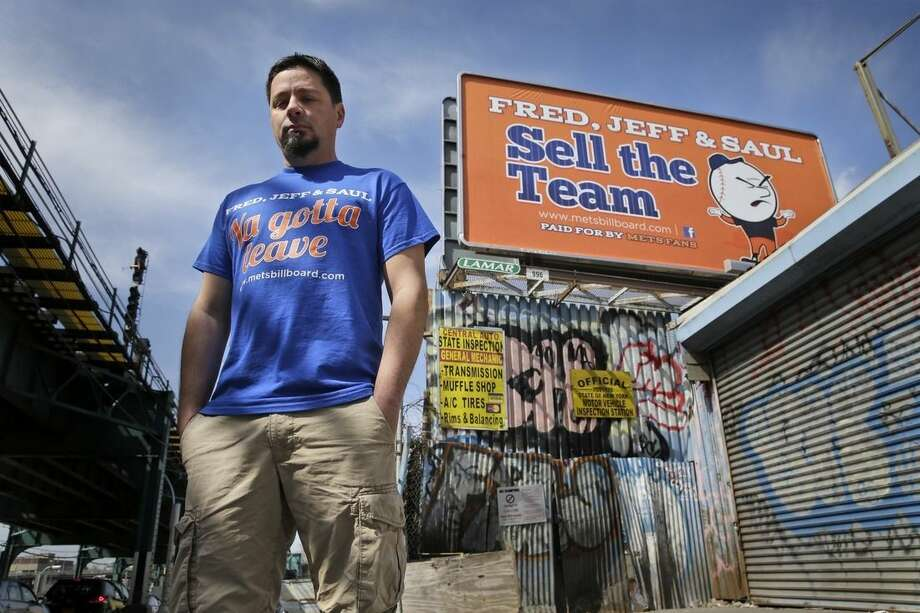 Gary Palumbo poses for a picture next to a billboard criticizing the ownership of the New York Mets across the street from Citi Field, Monday, April 13, 2015 in New York. Palumbo, a 39-year-old Mets fan who lives in New Hampshire, raised $6,700 on Kickstarter and paid for the billboards. (AP Photo/Seth Wenig)