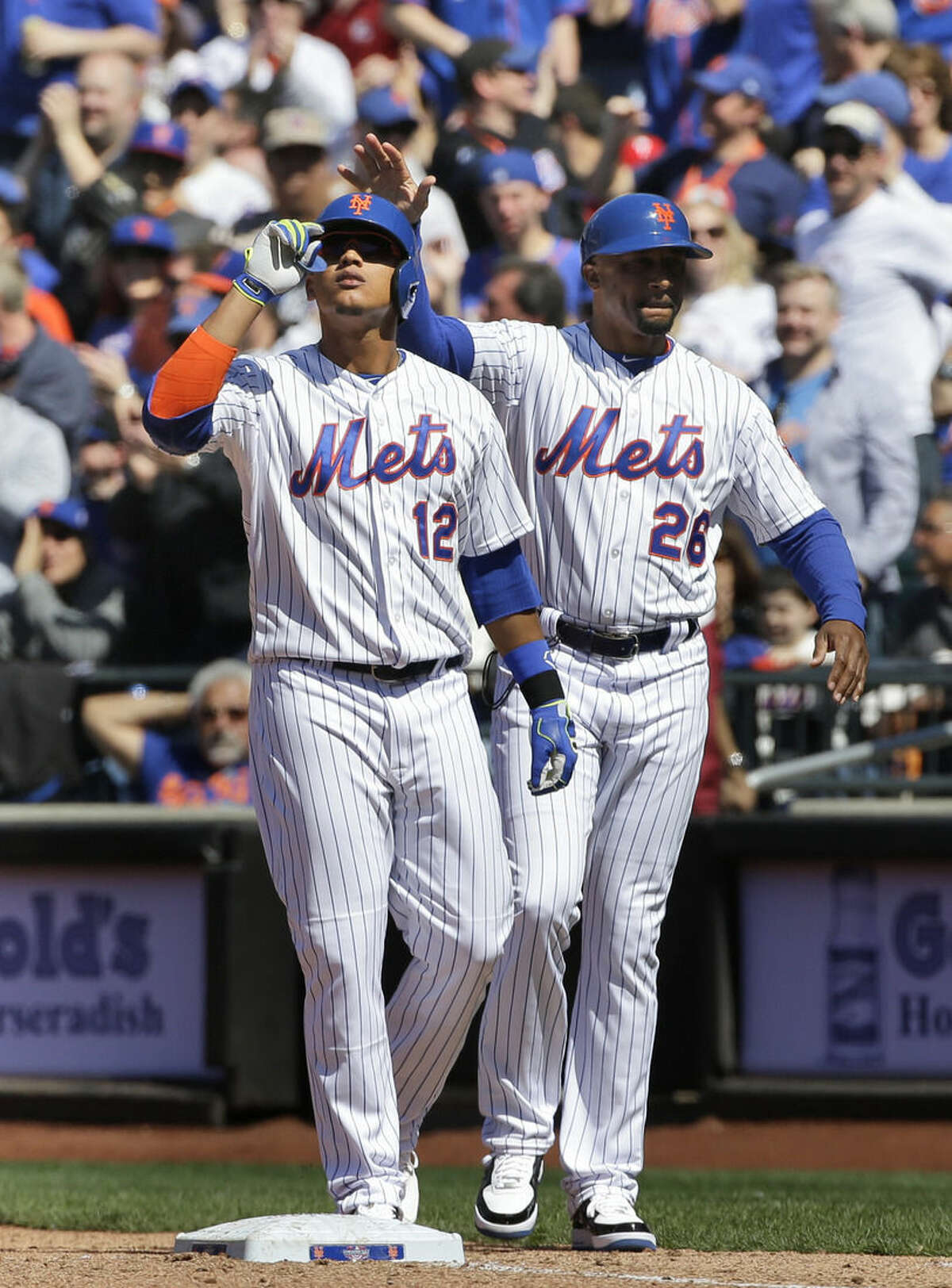 New York Mets' Juan Lagares, left, celebrates with first base coach Tom Goodwin after hitting an RBI single during the fourth inning of the baseball game against the Philadelphia Phillies at Citi Field, Monday, April 13, 2015 in New York. (AP Photo/Seth Wenig)