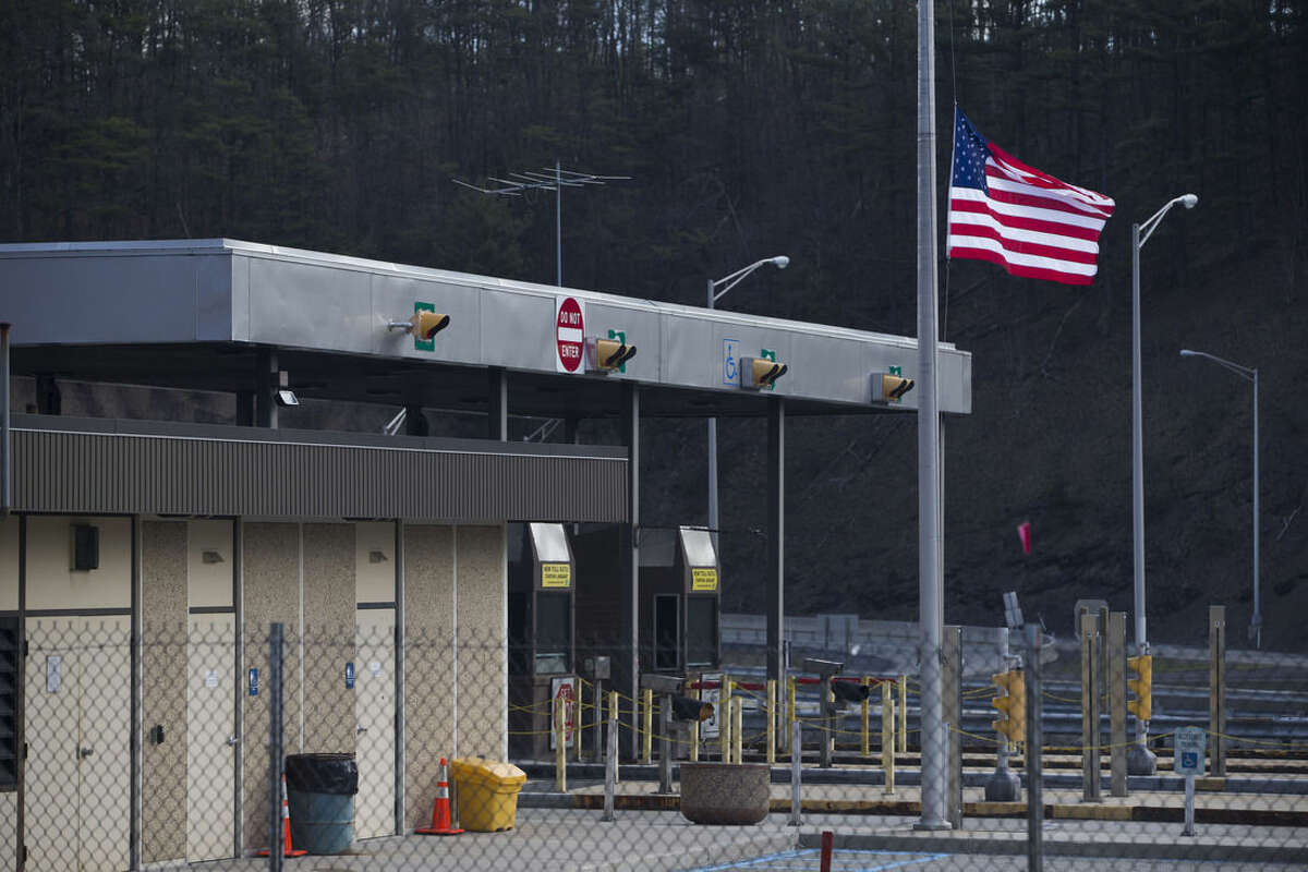FILE - In a Monday, March 21, 2016 file photo, the Fort Littleton Pennsylvania turnpike exit flies a U.S. flag at half mast after a shooting, in Littleton, Pa. Martha Berkstresser, a Pennsylvania Turnpike toll collector who survived the botched robbery attempt that left three people dead said she was terrified but her instincts took over during the attack by a retired state trooper, who was killed by police responding to her call for help. (Mark Pynes/PennLive.com via AP, File) MANDATORY CREDIT; MAGS OUT