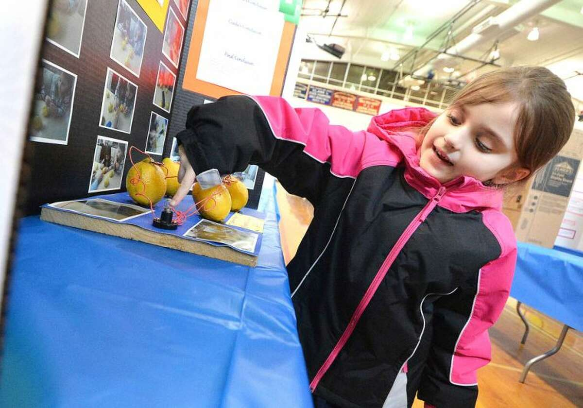 Hour Photo/Alex von Kleydorff Naramake School First Grader Giada Alfisi point to the bulb that will light when powered by lemons. The project her and her twin sister Bianca built is called Lemon-Tricity and will be judged at the Citywide Science Fair at Brien McMahon High School.