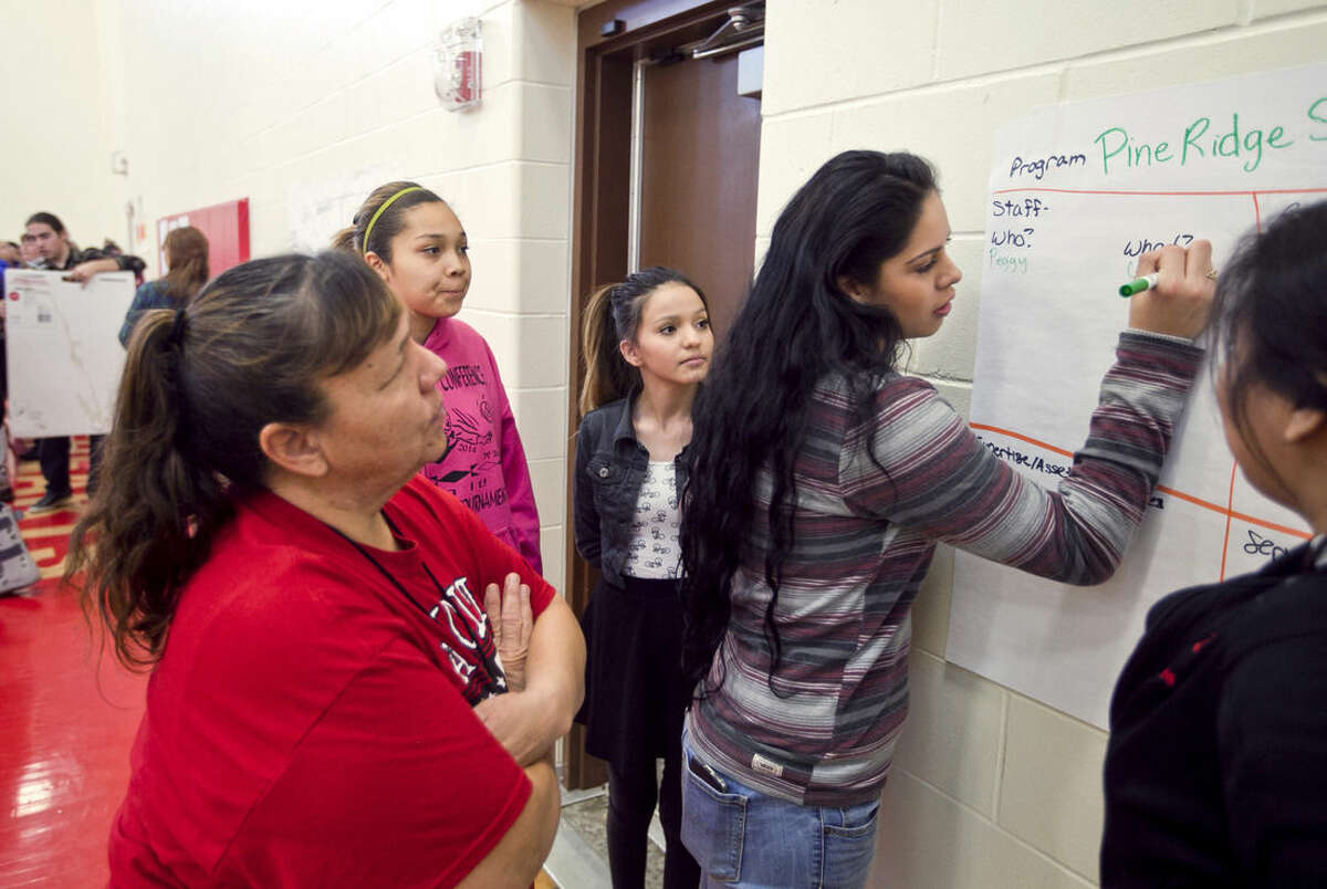 In this March 4, 2015 photo, Nellie Long, left, an education technician and coach at Pine Ridge High School, helps students, from left: Iman Hummingbird, Carrie Provost, Lynette Bettelyoun and Mariah Bravo as they write resources their school has to help students during three-day effort to find ways to prevent suicides on the Pine Ridge Indian Reservation in South Dakota. The people of the Pine Ridge Indian Reservation are no strangers to hardship or to the risk of lives being cut short. But a string of seven suicides by teenagers in recent months has shaken this impoverished community to its core and sent school and tribal leaders on an urgent mission to stop the deaths. (AP Photo/Rapid City Journal, Sean Ryan)