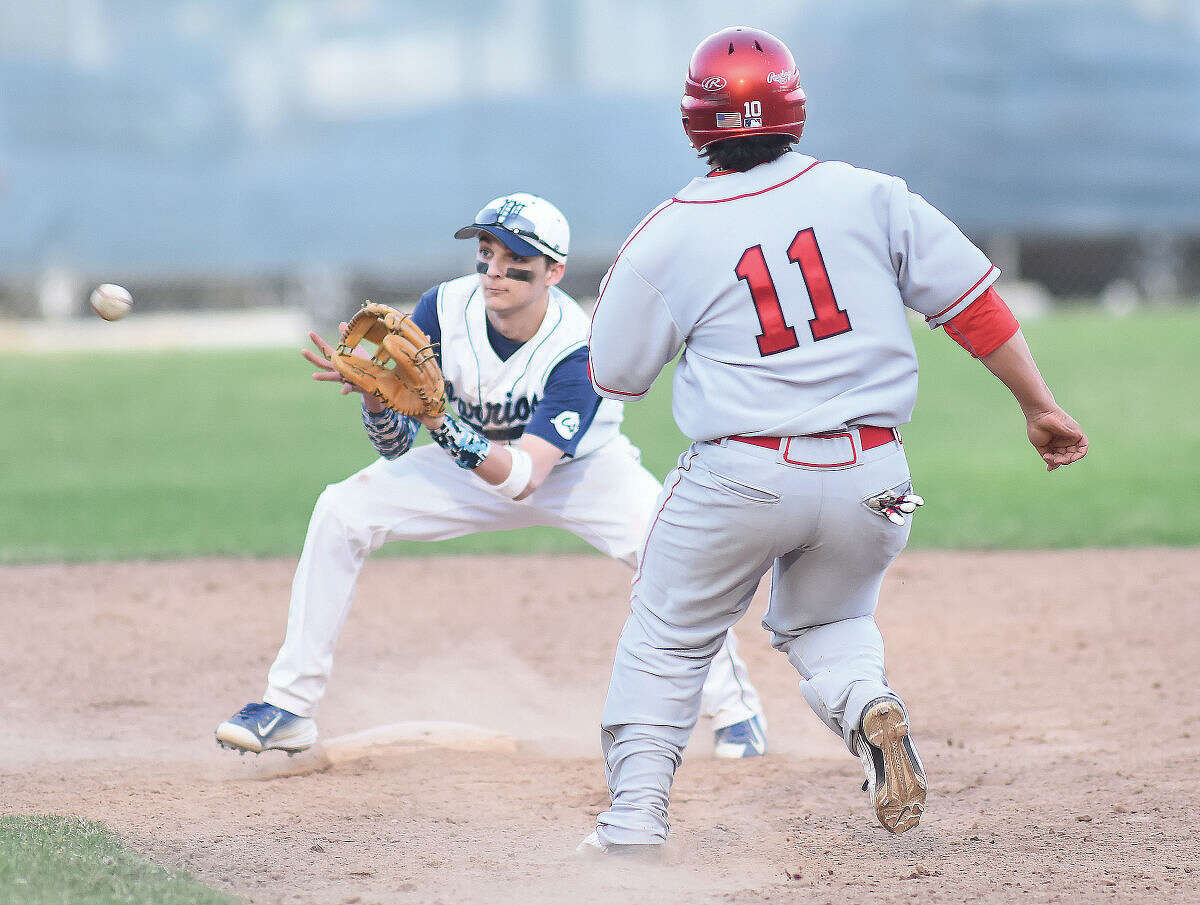 Hour photo/John Nash - Wilton shortstop Nate Johnson, left, waits for the ball as Greenwich's Marco Pastore is gunned down trying to steal second during Monday's FCIAC baseball game in Wilton.