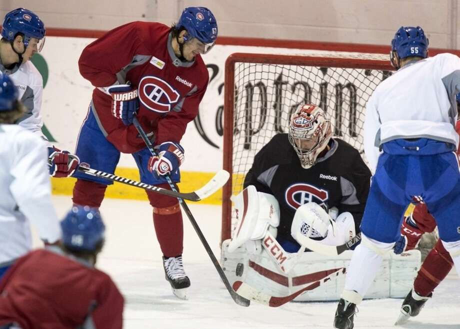 Montreal Canadiens' Max Pacioretty (67) plays the puck in front of goalie Carey Price during a practice Monday, April 13, 2015, in Brossard, Quebec. The Canadiens will face the Ottawa Senators in game one of the first round of NHL playoffs on Wednesday. (Paul Chiasson/The Canadian Press via AP)