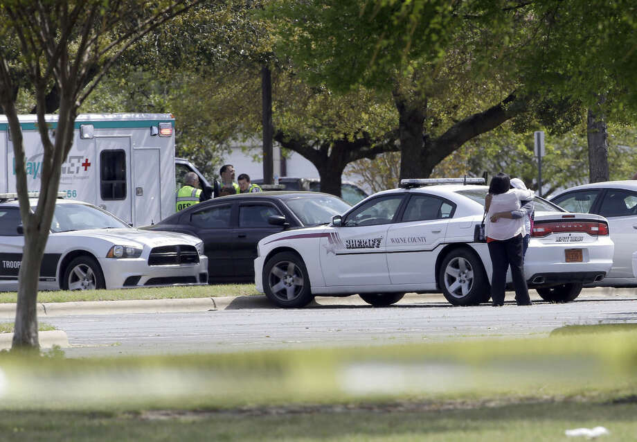 Two people hug as students and faculty wait outside Wayne Community College during a lockdown following a shooting on campus in Goldsboro, N.C., Monday, April 13, 2015. One person was killed in the shooting. (AP Photo/Gerry Broome)