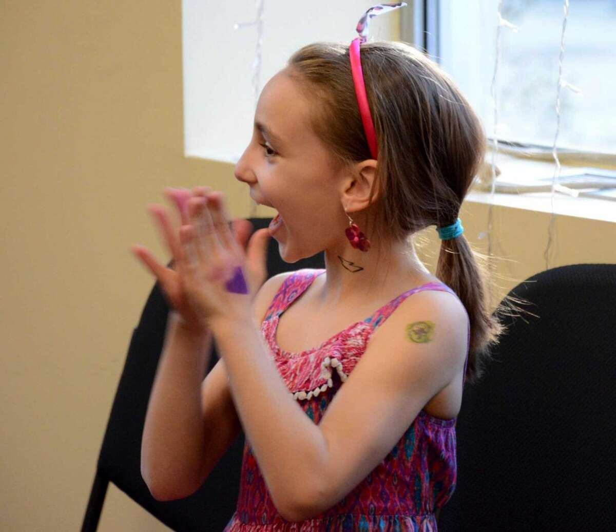 Alea Sauvageau, 7, from Bethel watches the yoyo perfomance at her families Kickstarter fundraiaer for Noteworthy Chocolates on Thursday April 14, 2016.