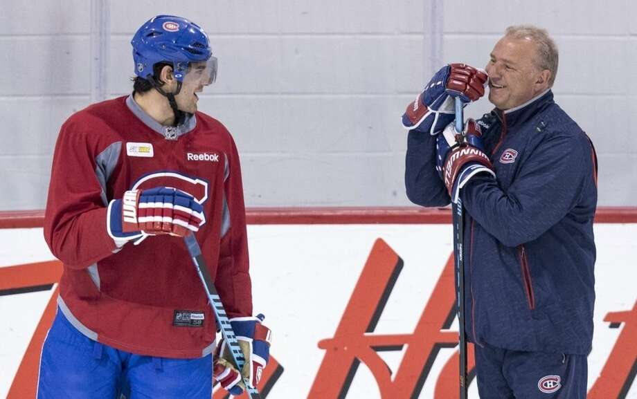 Montreal Canadiens head coach Michel Therrien, right, shares a laugh with Max Pacioretty during a practice Monday, April 13, 2015, in Brossard, Quebec. The Canadiens will face the Ottawa Senators in game one of the first round of NHL playoffs on Wednesday. (Paul Chiasson/The Canadian Press via AP)