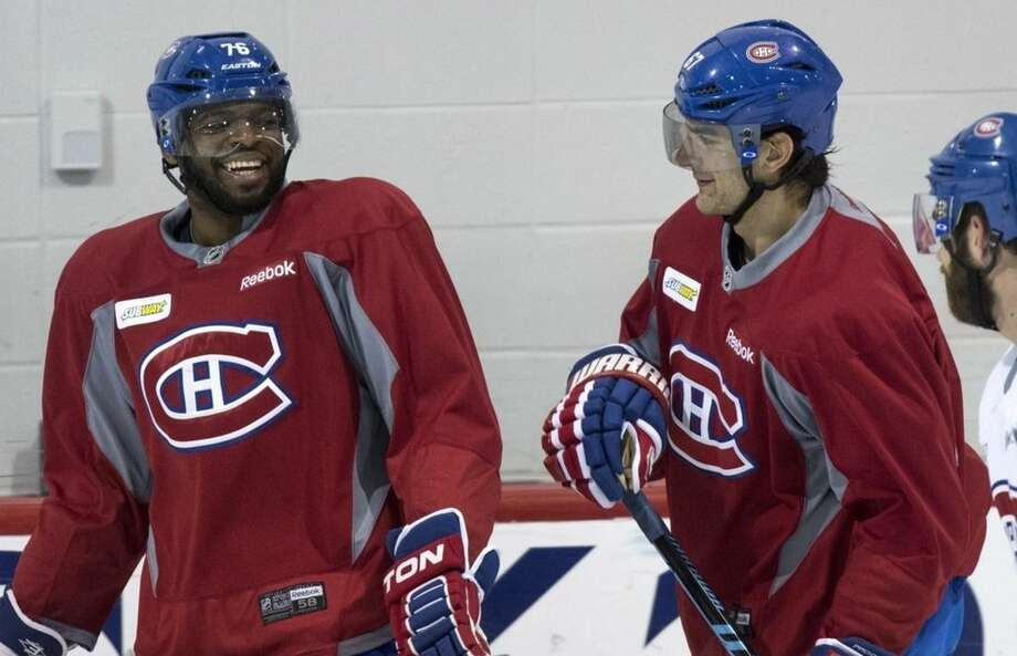 Montreal Canadiens' P.K. Subban, left, shares a laugh with teammate Max Pacioretty during a practice, Monday, April 13, 2015, in Brossard, Quebec. The Canadiens will face the Ottawa Senators in game one of the first round of NHL playoffs on Wednesday. (Paul Chiasson/The Canadian Press via AP)