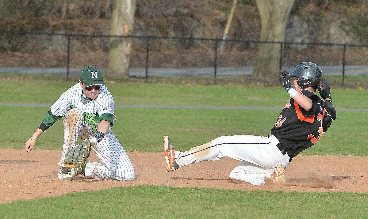 Norwalk shortstop Eddie McCabe reaches for the ball at second base as a Ridegfield base runner slides into second base. (Hour photo/Alex von Kleydorff)