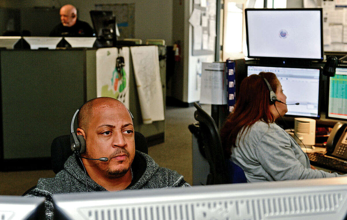 Emergency dispatcher Eric Giddiens takes calls in the third-floor dispatch office at Norwalk Police Department Friday, April 15, 2016.