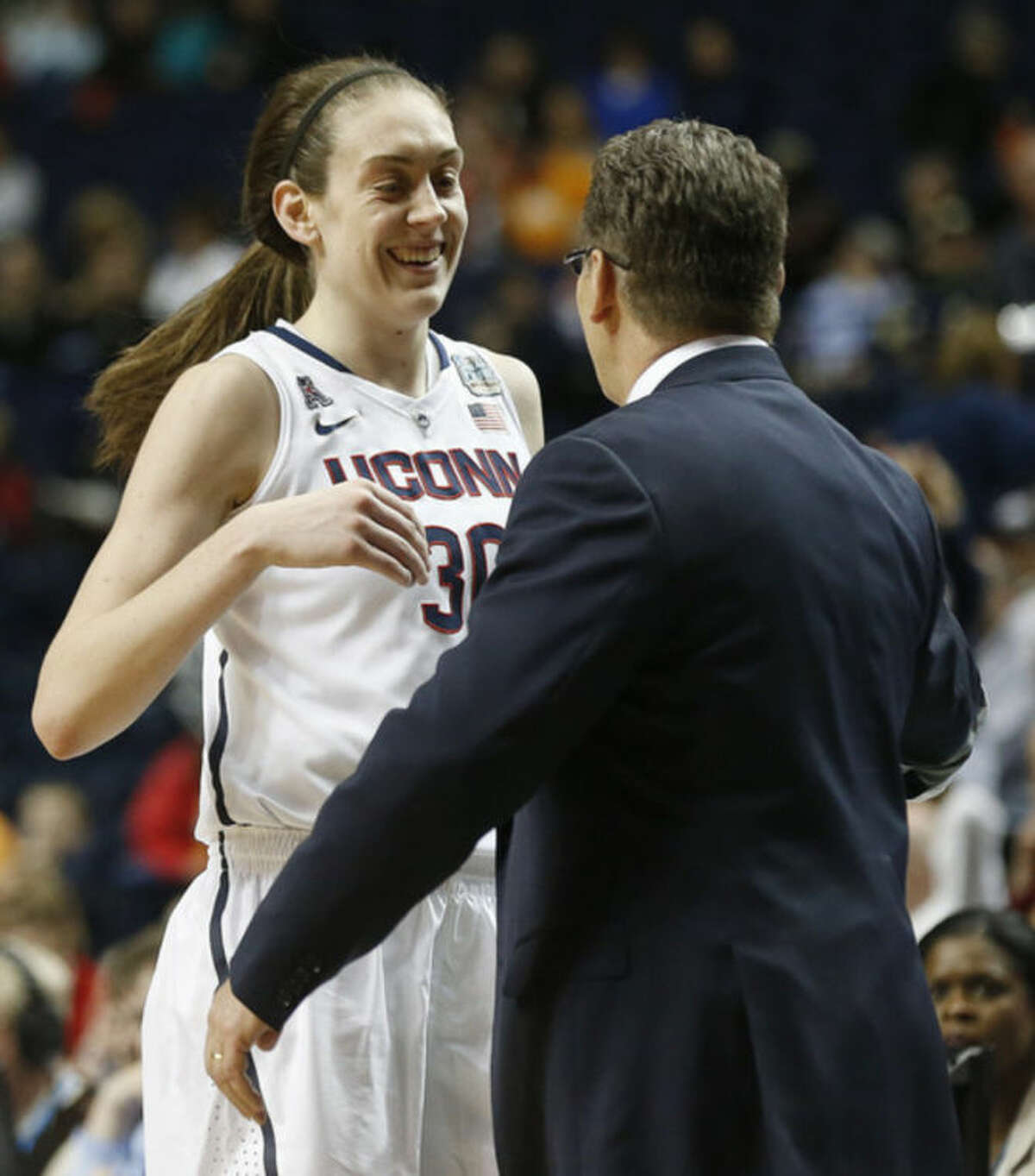 Connecticut forward Breanna Stewart (30) prepares to hug Connecticut head coach Geno Auriemma after the second half of the semifinal game in the Final Four of the NCAA women's college basketball tournament, Sunday, April 6, 2014, in Nashville, Tenn. Connecticut won 75-56. (AP Photo/John Bazemore)