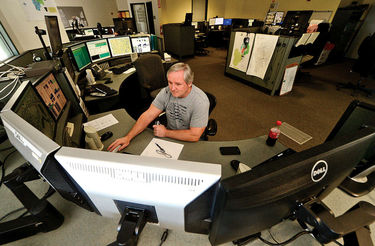 Emergency dispatcher Mike Devaney takes calls in the third-floor dispatch office at Norwalk Police Department Friday, April 15, 2016.