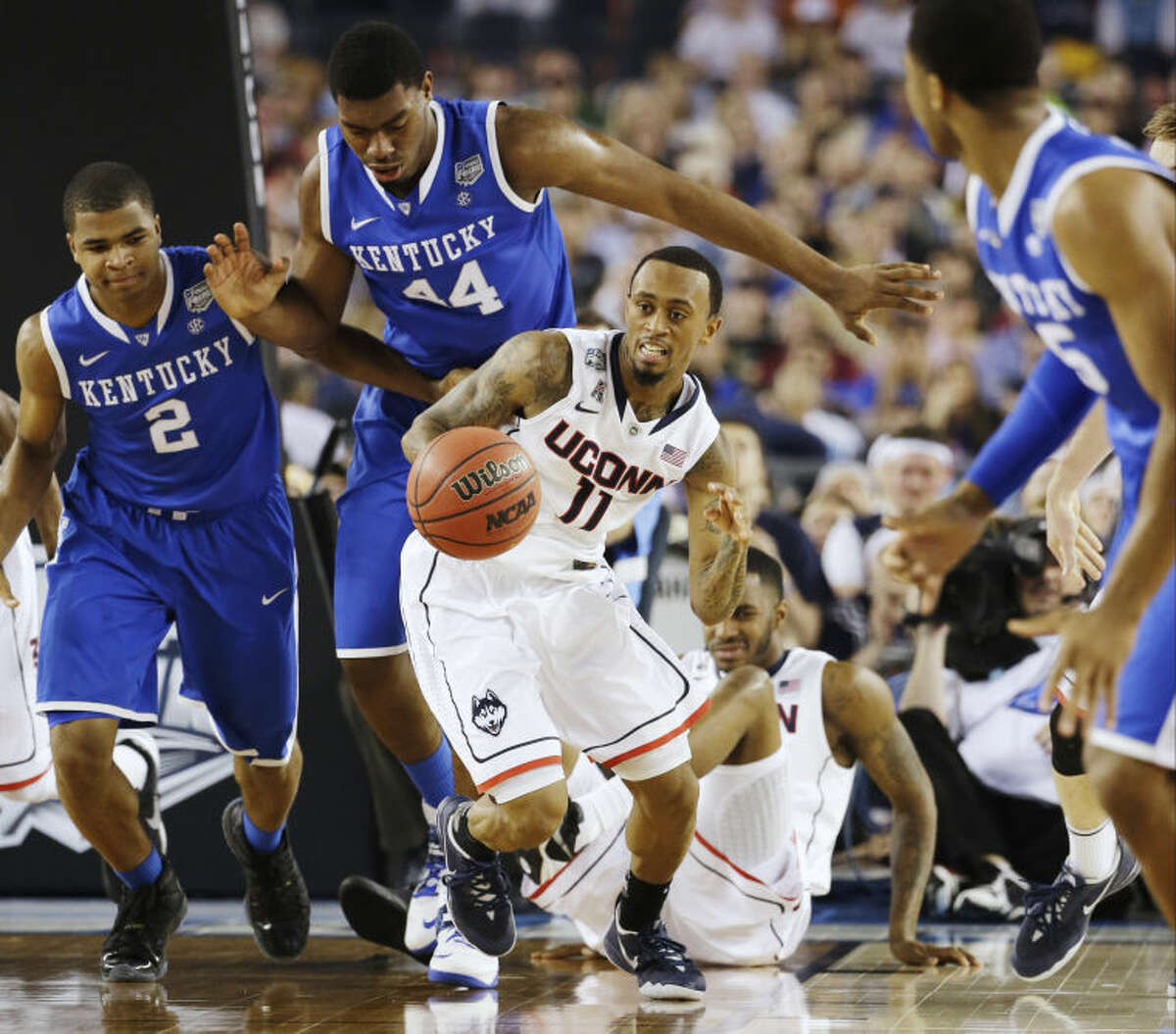 Connecticut guard Ryan Boatright (11) gets past Kentucky guard Aaron Harrison (2), pk44n=, as guard Andrew Harrison (5) looks on during the first half of the NCAA Final Four tournament college basketball championship game Monday, April 7, 2014, in Arlington, Texas. (AP Photo/David J. Phillip)