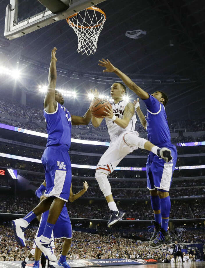 Connecticut guard Shabazz Napier shoots between Kentucky center Dakari Johnson (44) and guard James Young (1), right, during the first half of the NCAA Final Four tournament college basketball championship game Monday, April 7, 2014, in Arlington, Texas. (AP Photo/David J. Phillip)