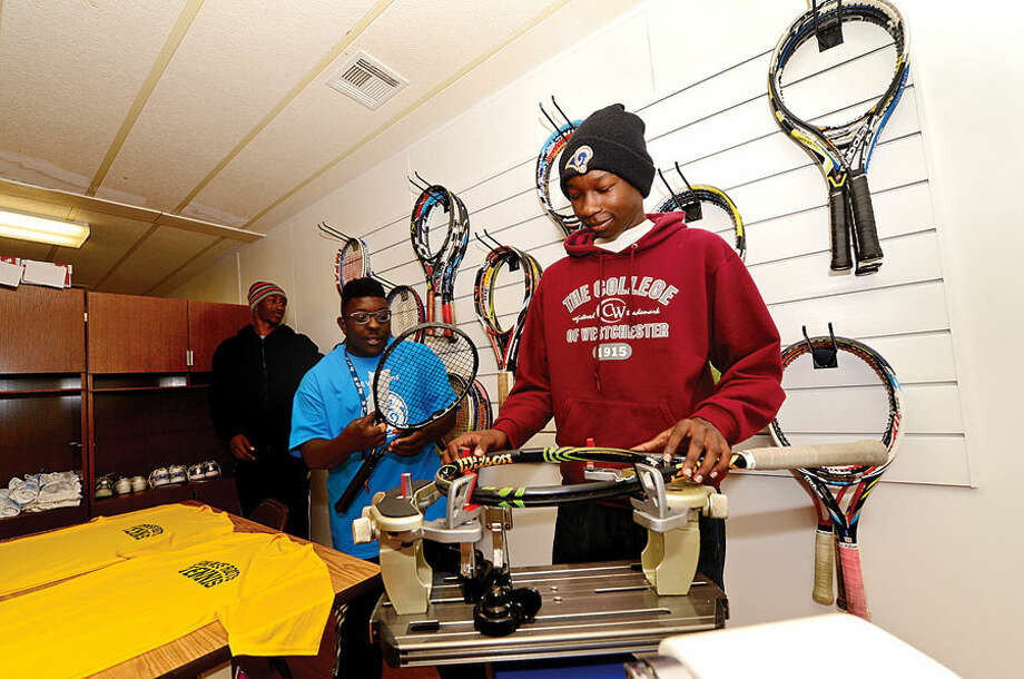 Hour photo / Erik Trautmann Norwalk Grass Roots program participant Jalen Dennison looks over the stringing room following the ribbon-cutting ceremony for the new Grass Roots headquarters and youth center at the old Nathaniel Ely School at 11 Ingalls Ave. Friday. GE Capital volunteers spent three days renovating the space for the grand opening.