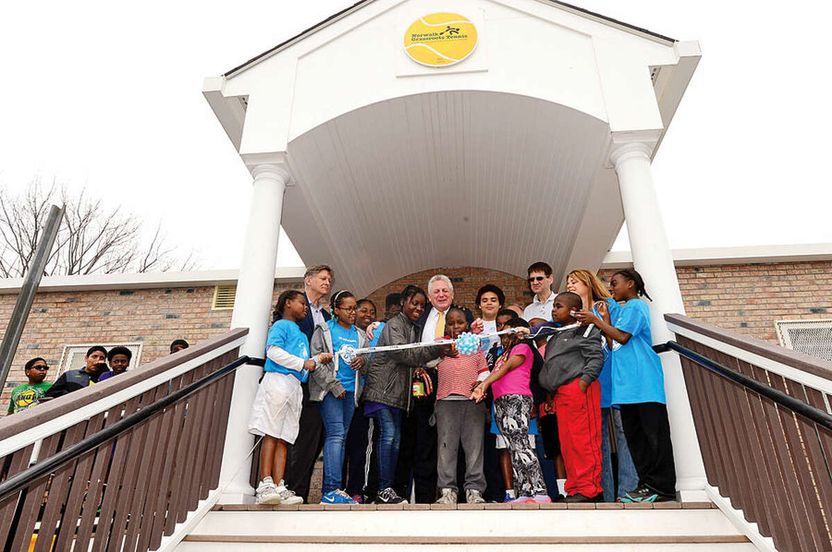 Hour photo / Erik Trautmann Mayor Harry Rilling and paricipants of the Norwalk Grass Roots Tennis program assist in the ribbon-cutting ceremony for the new Grass Roots headquarters and youth center at the old Nathaniel Ely School at 11 Ingalls Ave. Friday. GE Capital volunteers spent three days renovating the space for the grand opening.