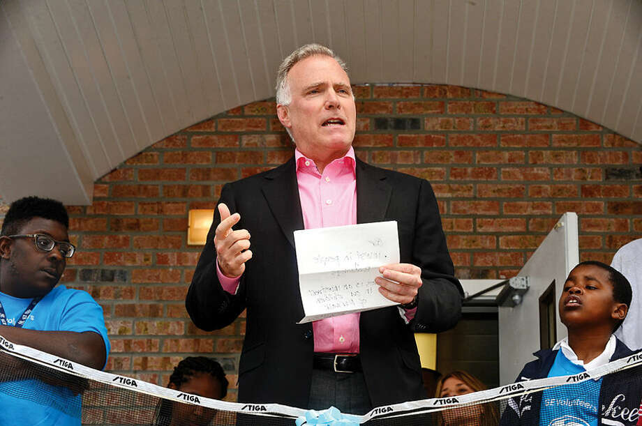 Hour photo / Erik Trautmann GE Capital President and CEO Alec Burger spekas during the Norwalk Grass Roots Tennis ribbon-cutting ceremony for their new headquarters and youth center at the old Nathaniel Ely School at 11 Ingalls Ave. Friday. GE Capital volunteers spent three days renovating the space ready for grand opening.