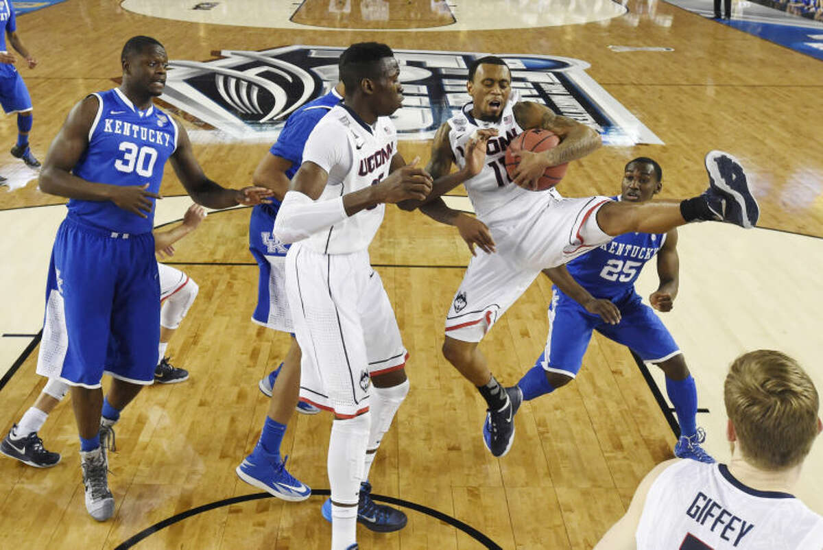 Connecticut guard Ryan Boatright (11) comes down with the ball as Kentucky forward Julius Randle (30), center Amida Brimah (35) and guard Dominique Hawkins (25) look on during the first half of the NCAA Final Four tournament college basketball championship game Monday, April 7, 2014, in Arlington, Texas. (AP Photo/Chris Steppig, pool)