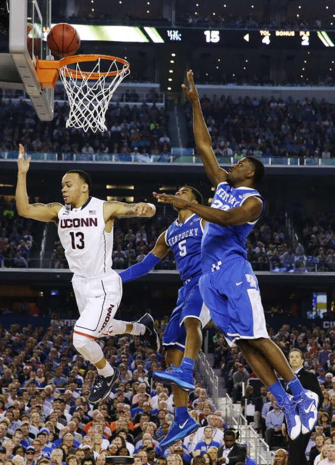 Connecticut guard Shabazz Napier (13) puts up the ball against Kentucky guard Andrew Harrison (5) and forward Alex Poythress (22) during the first half of the NCAA Final Four tournament college basketball championship game Monday, April 7, 2014, in Arlington, Texas. (AP Photo/David J. Phillip)