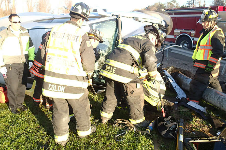 Firefighters work to remove the driver from a car that struck a pole on Interstate 95 and flipped on its side Saturday morning.