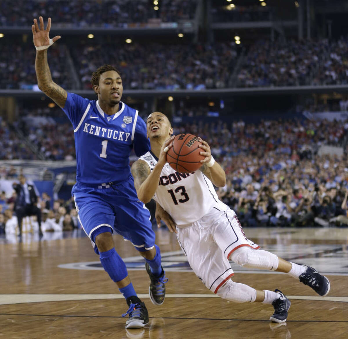 Connecticut guard Shabazz Napier, right, drives past Kentucky guard James Young during the first half of the NCAA Final Four tournament college basketball championship game Monday, April 7, 2014, in Arlington, Texas. (AP Photo/David J. Phillip)