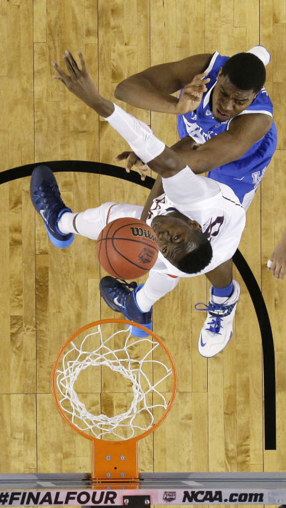 Kentucky center Dakari Johnson, top, fights for a rebound with Connecticut center Amida Brimah during the first half of the NCAA Final Four tournament college basketball championship game Monday, April 7, 2014, in Arlington, Texas. (AP Photo/David J. Phillip)