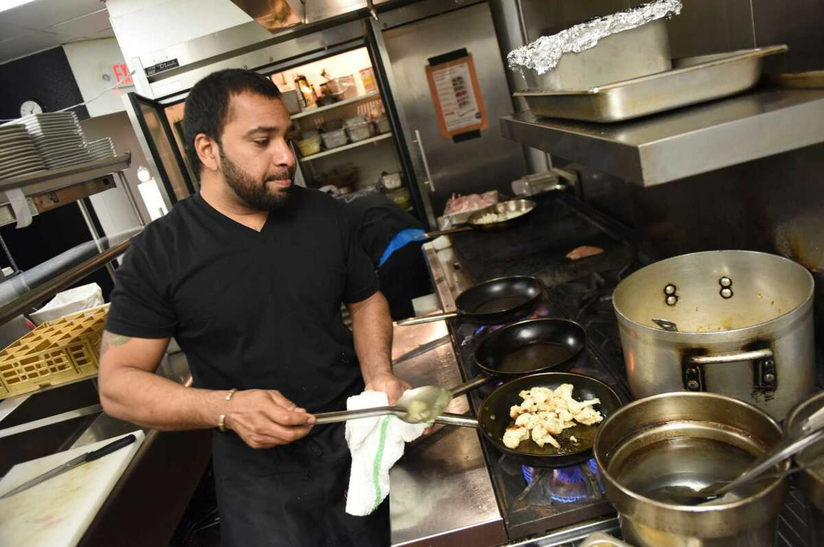 Chef Shelby Kozhiparambal cooks a meal in the kitchen at The Fez Morrocan-inspired restaurant and wine bar in downtown Stamford on Monday.