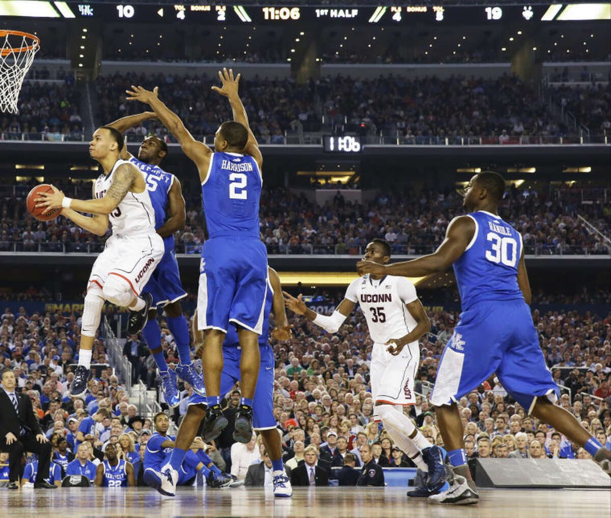 Connecticut guard Shabazz Napier shoots between Kentucky guard Dominique Hawkins (25) and guard Aaron Harrison (2) during the first half of the NCAA Final Four tournament college basketball championship game Monday, April 7, 2014, in Arlington, Texas. (AP Photo/David J. Phillip)