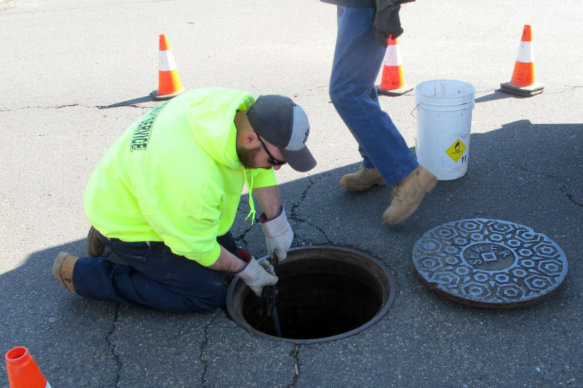 A crew from Milford's Wastewater division clean out a clog formed by wipes and grease Friday morning at the intersection of Buckingham Avenue and Vine Street. The site is one of 55 known trouble spots in the city's 225 mile sewer system.