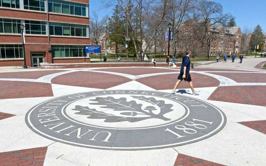 """A student walks across the University of Connecticut seal on the Storrs campus """"Learning Communities."""" Thursday, April 14, 2016, in Storrs, Conn."""