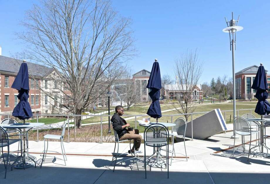 A student sits on a patio on the Student Union Mall of the University of Connecticut campus, on Thursday, April 14, 2016, in Storrs, Conn.