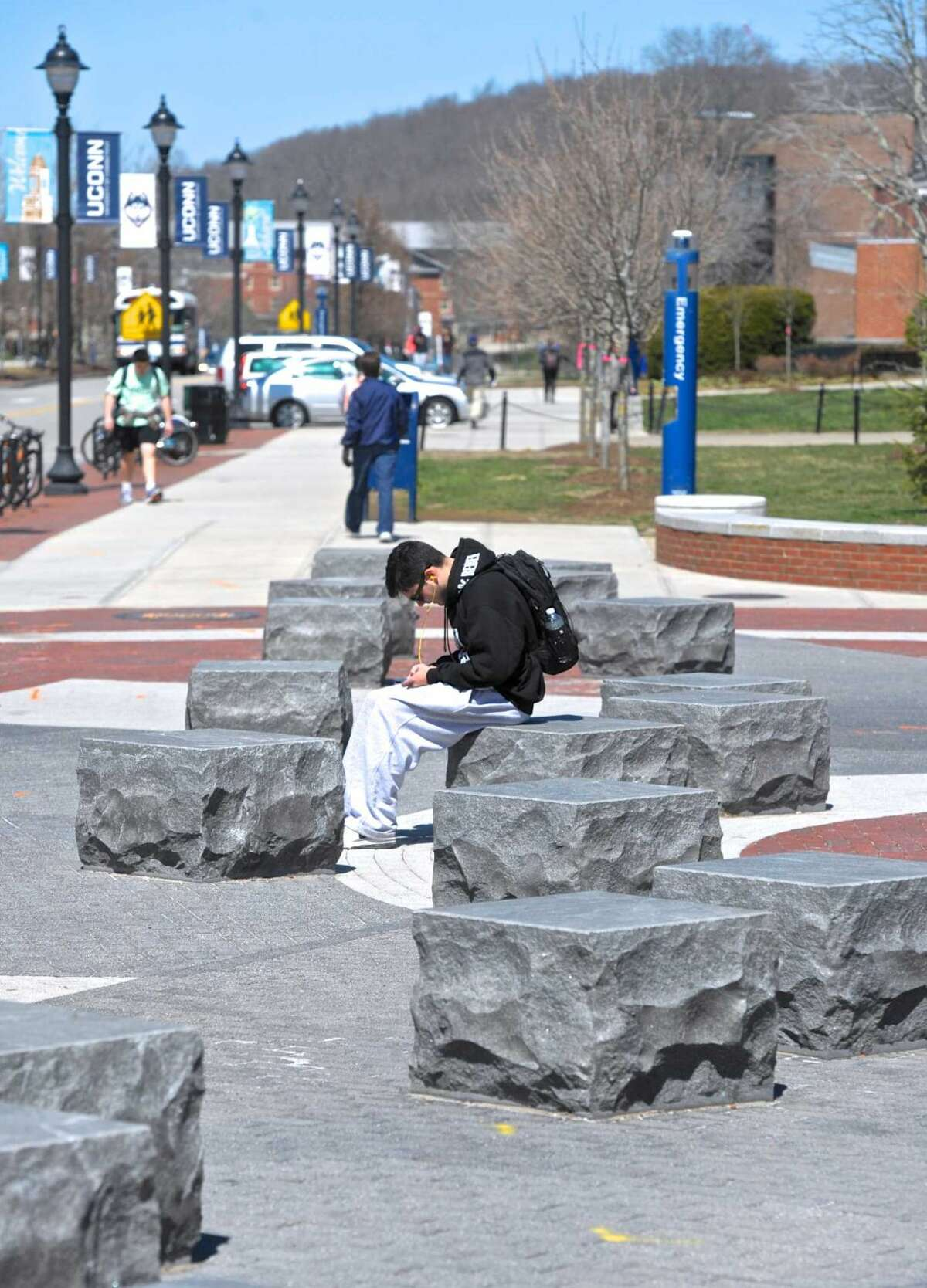 A student sits in front of the University of Connecticut student union on Thursday, April 14, 2016, in Storrs, Conn.
