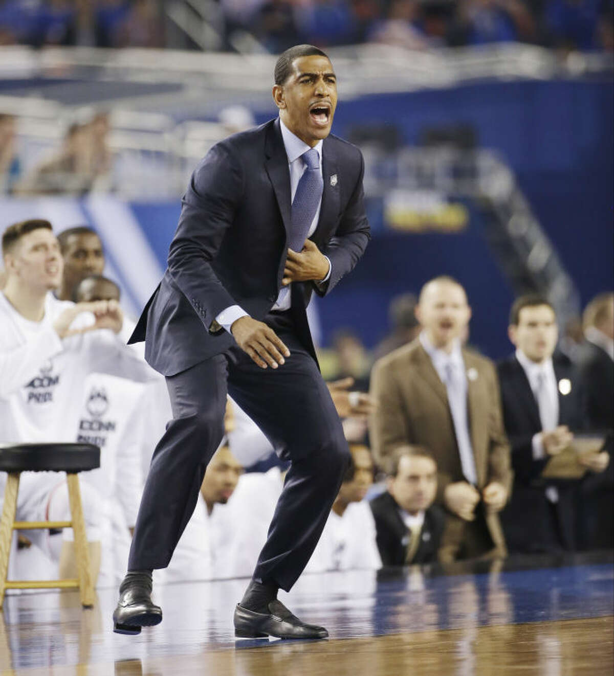 Connecticut head coach Kevin Ollie directs action from the sideline against Kentucky during the first half of the NCAA Final Four tournament college basketball championship game Monday, April 7, 2014, in Arlington, Texas. (AP Photo/David J. Phillip)