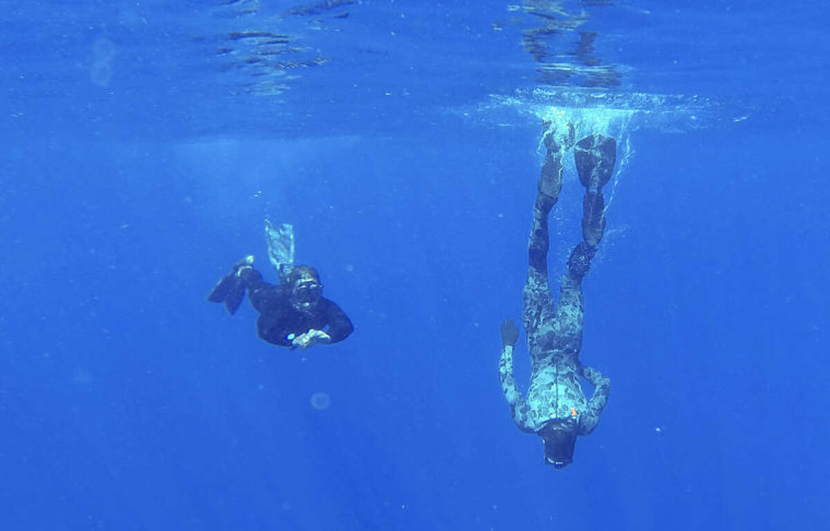 In this April 7, 2014 photo provided by the Australian Defense Force Able Seaman Clearance Divers Matthew Johnston, right, and Michael Arnold, from the Australian Defense Vessel Ocean Shield, scan the water for debris from the missing Malaysia Airlines Flight 370 in the southern Indian Ocean. Up to 14 planes and as many ships were focusing on a single search area covering 77, 580 square kilometers (29,954 square miles) of ocean, 2,270 kilometers (1,400 miles) northwest of the Australian west coast city of Perth, Australia. (AP Photo/Australian Defense Force, Lt. Ryan Davis) EDITORIAL USE ONLY