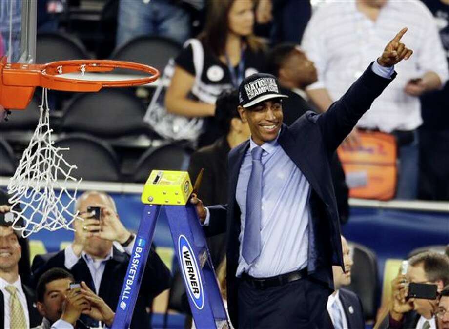 Connecticut head coach Kevin Ollie celebrates while cutting down the net after beating Kentucky 60-54, at the NCAA Final Four tournament college basketball championship game Monday, April 7, 2014, in Arlington, Texas. (AP Photo/Tony Gutierrez) / AP