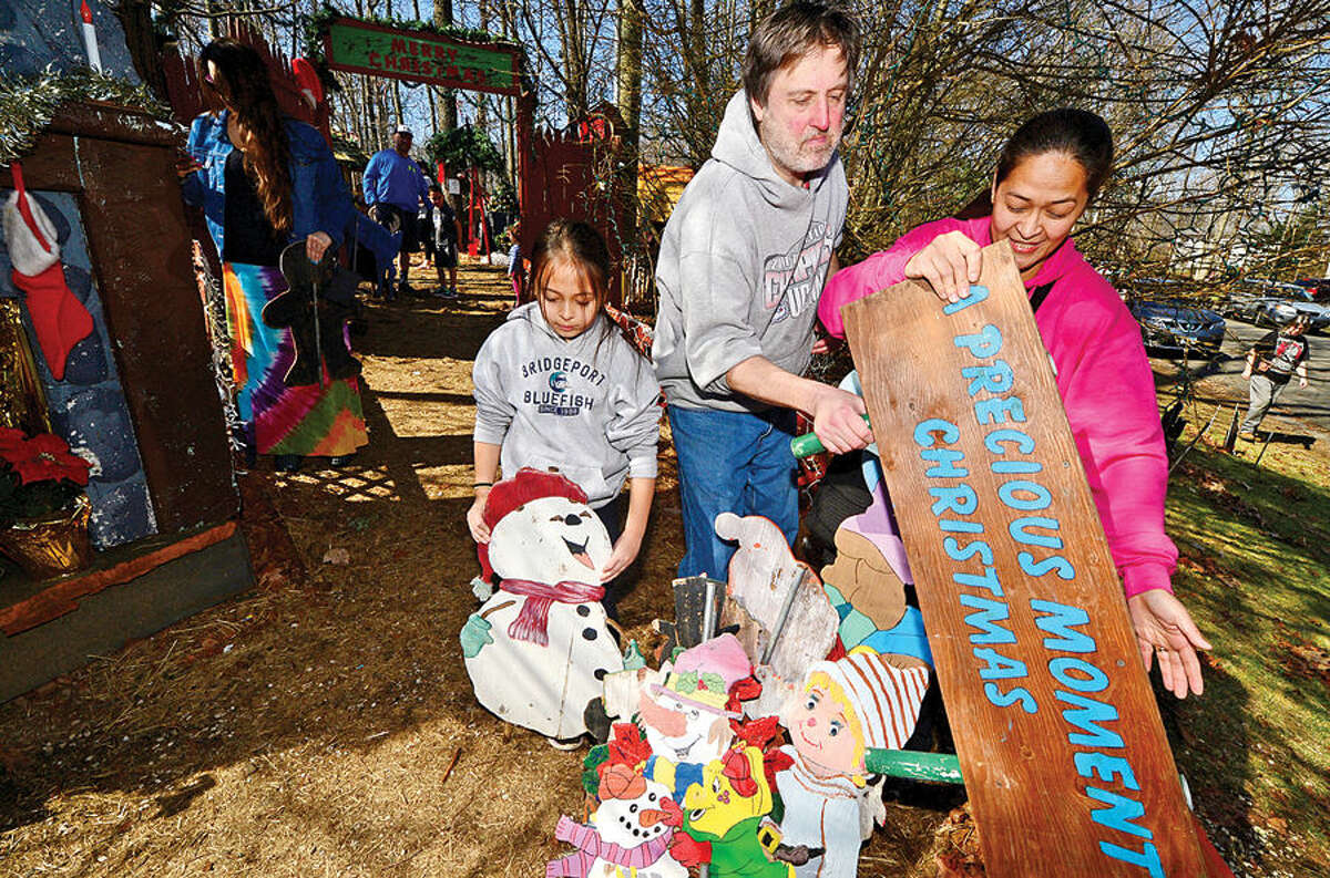 Hour photo / Erik Trautmann May, Mark and Maekaela Fallo pick out Christmas decorations at the home of Rick and Joan Setti Saturday, whose elaborate Midwood Road Christmas display has delighted Norwalkers for 26 years, during a tag sale of more than 400 hand-carved figures and thousands of lights.