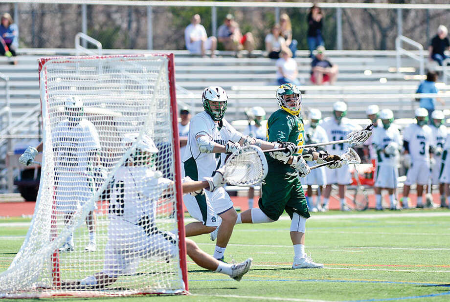 Hour photo / Erik Trautmann Trinity Catholic's #2 watches his shot go in the goal during their lacrosse game against NorwalkSaturday