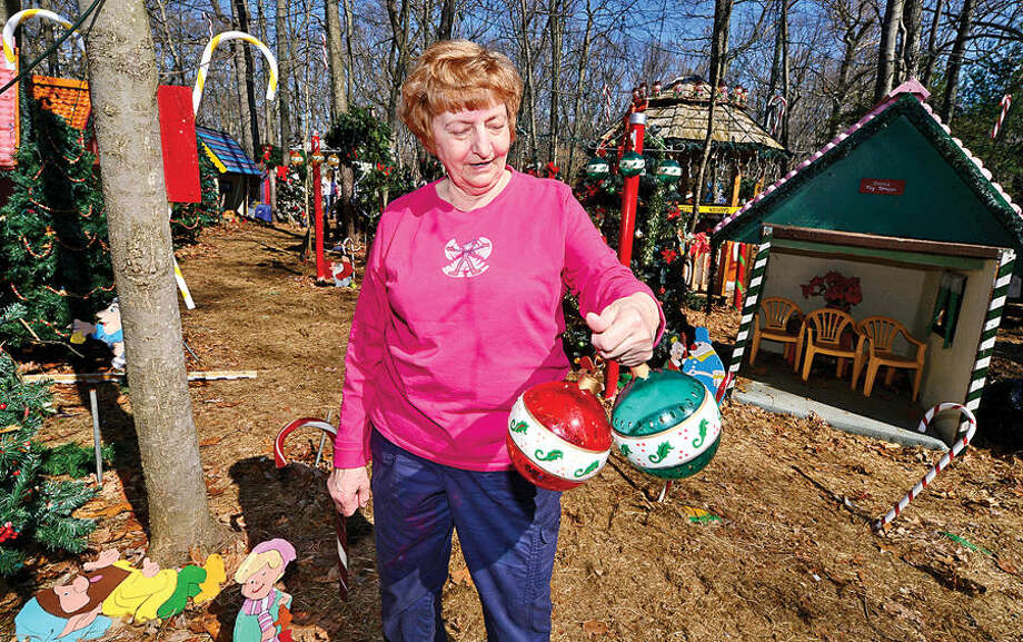 Hour photo / Erik Trautmann Gerri Grasso picks out Christmas decorations at the home of Rick and Joan Setti Saturday, whose elaborate Midwood Road Christmas display has delighted Norwalkers for 26 years, during a tag sale of more than 400 hand-carved figures and thousands of lights.