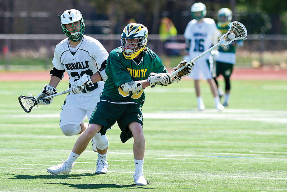 Hour photo / Erik Trautmann Norwalk's Joseph laracca follows Trinity Catholic's #Liam Shanahan during thier lacrosse game Saturday