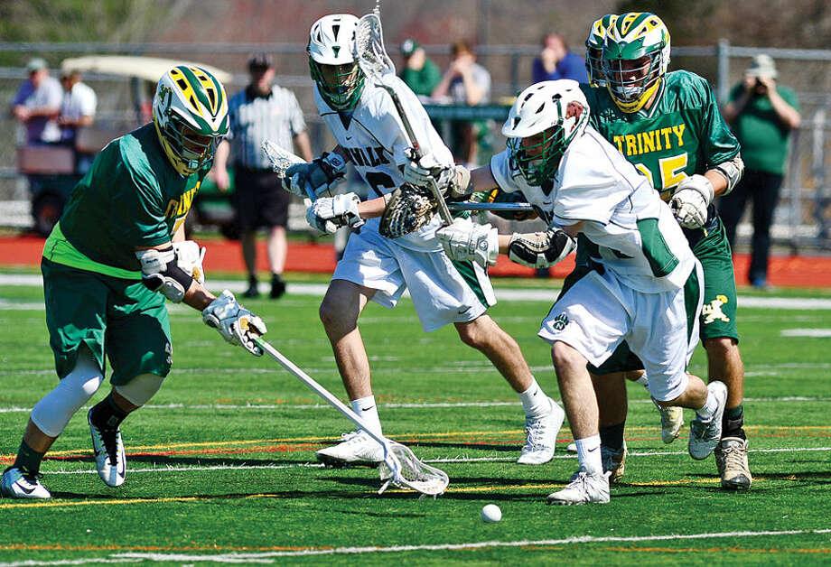 Hour photo / Erik Trautmann Norwalk's #24 Nicholas Arcario battles #7 Kyle Pryzpek during thier lacrosse game against Trinity Catholic Saturday