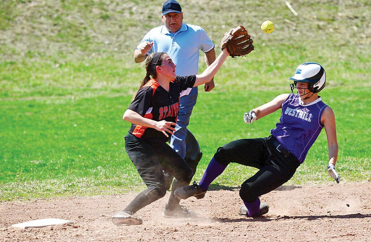 Hour photo / Erik Trautmann Westhill's Emma Hart slides under shortstop Allie Buzzeo during their softball game against Stamford High School Saturday.