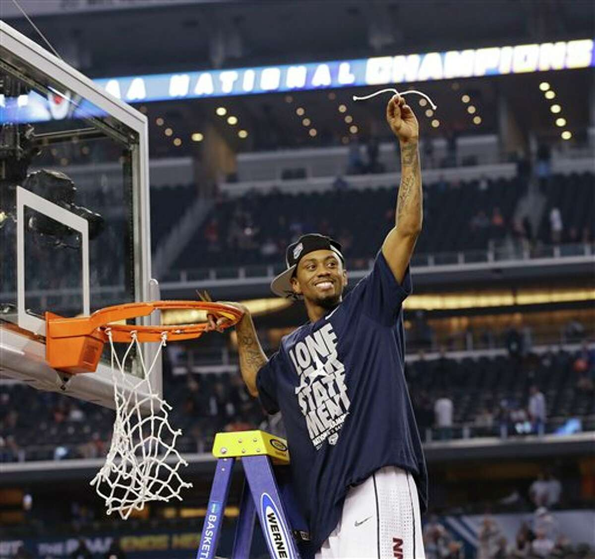 Connecticut guard Ryan Boatright cuts down the net after beating Kentucky 60-54, at the NCAA Final Four tournament college basketball championship game Monday, April 7, 2014, in Arlington, Texas. (AP Photo/David J. Phillip)