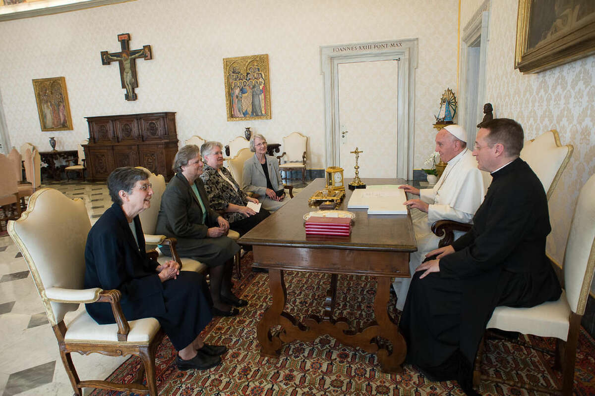 Pope Francis, second right, talks with a delegation of The Leadership Conference of Women Religious during an audience in the pontiff's studio at the Vatican, Thursday, April 16, 2015. The Vatican has announced the unexpected conclusion of a controversial overhaul of the main umbrella group of US nuns in a major shift in tone and treatment of American nuns under the social justice-minded Pope Francis. (L'Osservatore Romano/Pool Photo via AP)